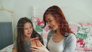 Little cute girl giving gift box to her young happy mom celebrating mothers day sitting on bed in
