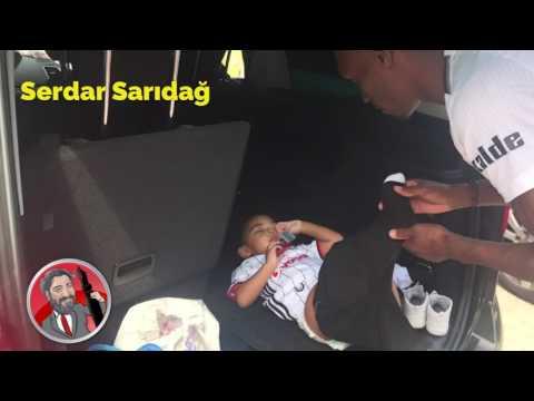 Atiba, oğlu Noah'ı, arabanın bagajında giydiriyor.