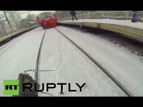 クレイジーなロシアの男が電車にロープを付けてスキー。