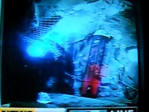CHILE: LAST PERSON UNDERGROUND IN MINE, CHILEAN RESCUE WORKER LOADING IN & GOING UP