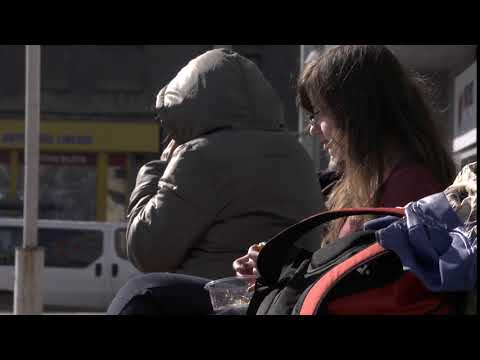 A student girl is eating fastfood salad with a roll while waiting for a bus Free HD video footage