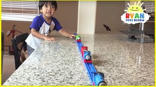 Ryan plays with Thomas and Friends trains around the house
