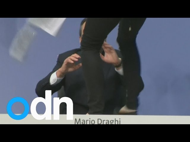 Protester showers ECB President Draghi with confetti at conference