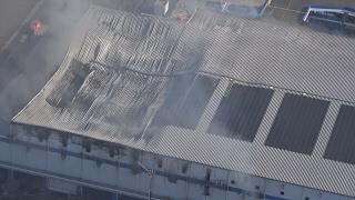 倉庫火災、消火活動続く