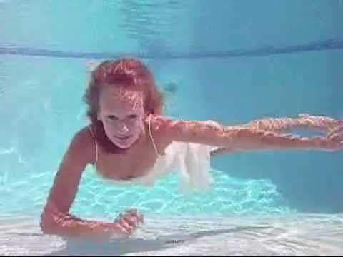 Girl swimming in pool in a dress