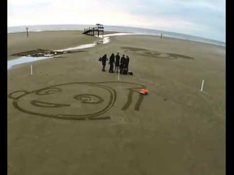 Robot artist draws giant sketch on the beach