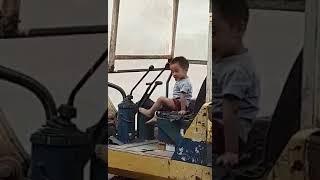 bé tập lái máy xúc.