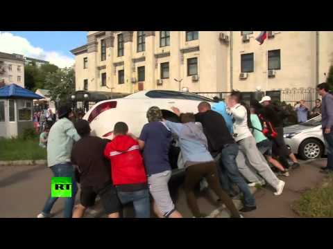 Kiev protesters turn over cars, drag down flag, pile up tires at Russian embassy