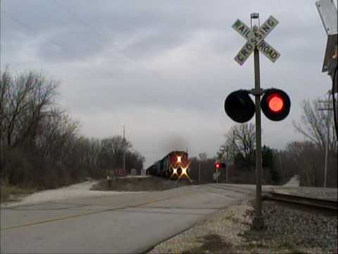 A northbound Canadian National freight train crossing Honey Creek Road near Honey Creek, WI. The 78.7 defect detector gives a read out after the train passes...