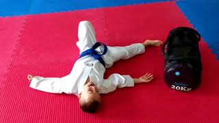 Child fitness - taekwondo training. Young Pawel doing a workout to get big and strong.