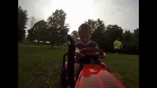 Kid on 12V Power Wheels Case Tractor with Trailer