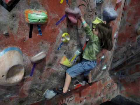 Alisa making up a boulder problem in a gym