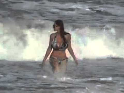 Busty bikini-clad girl comes in from the surf