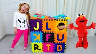 Ulya playing with alphabet blocks and new toy dolls