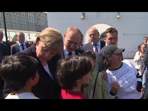 Putin, Merkel cuddle kids, take photos in Kremlin