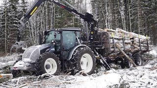 Valtra A124 forestry tractor logging in winter forest