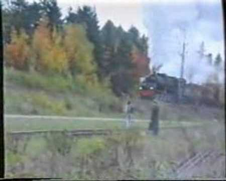 A hardworking steam turbine engine pulls heavy timber train