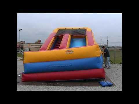 rolling up an 18' inflatable slide from Bounce About Party Rentals LLC