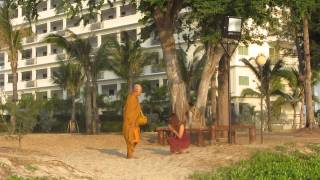 Thai Buddhist monk accepting money on his alms round from a girl on the beach near Hua Hin