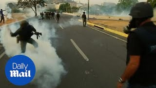 Security forces fire tear gas outside La Carlota airbase in Caracas