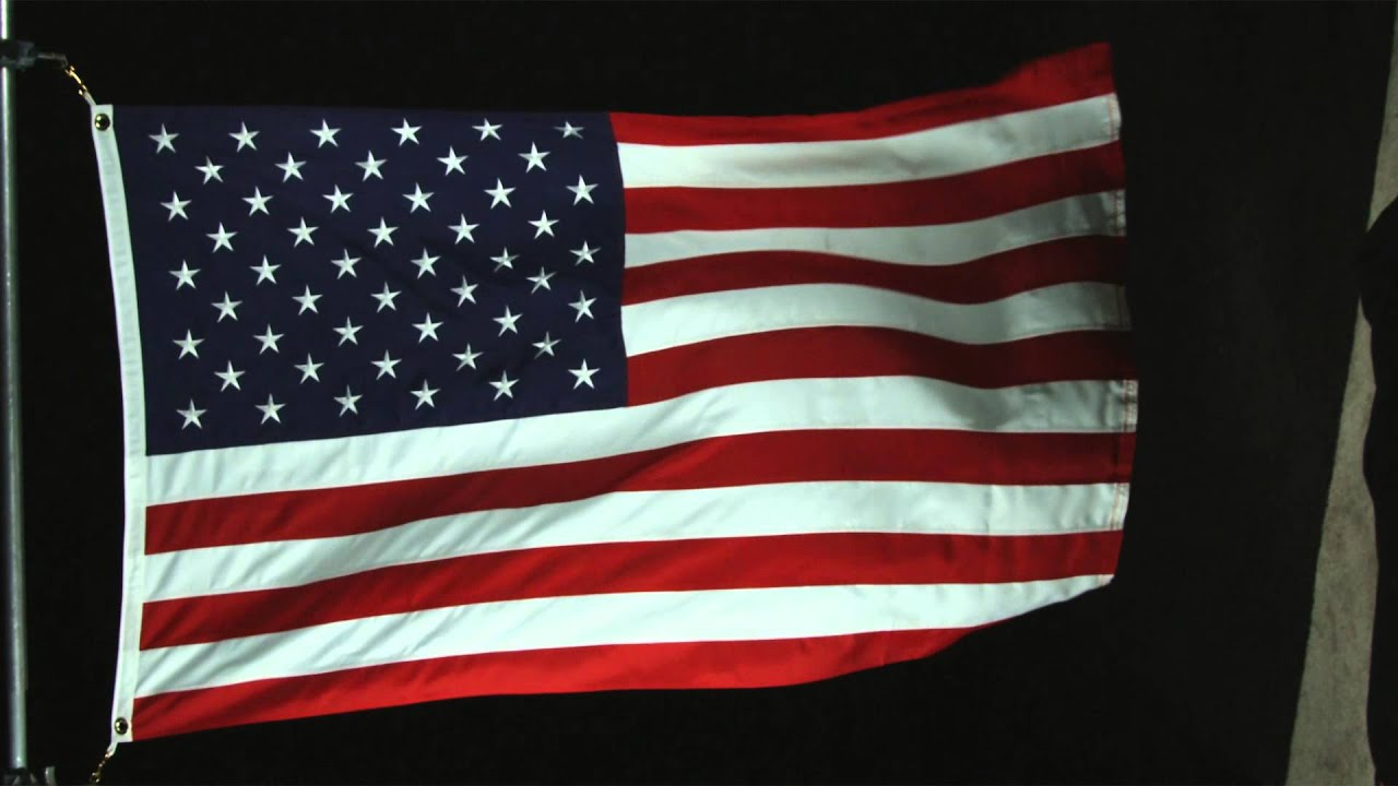 The American flag waving in the wind with black background ...