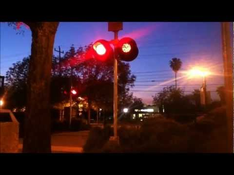 Pedestrian railroad crossing signals with union pacific freight train and light rail train