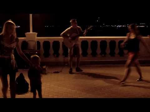 Прикольный уличный гитарист круто играет на набережной на Черном море в Геленджике на день города
