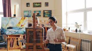 Female art teacher is working with good-looking young girl student painting picture giving advice