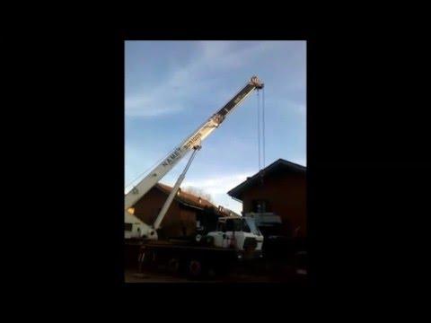 Autogru solleva un mini scavatore Mobile crane lifts a mini excavator