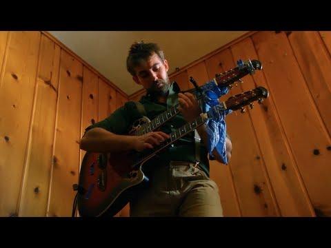 """Un tipo tocando el tema """"Dueling Banjos"""" en una guitarra de doble mástil"""
