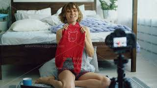 Attractive cheerful woman sitting near bed recording video blog about knitting children's clothes at