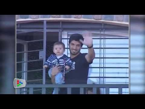 Suarez waves at his supporters from his balcony