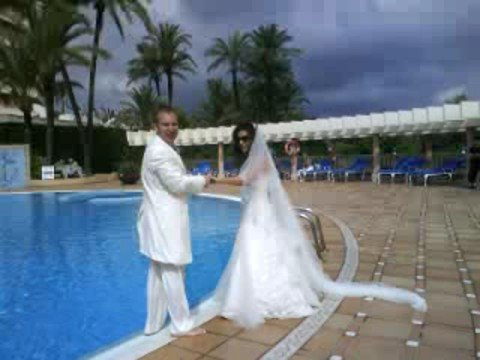 Newly weds jump in the pool in their wedding outfits