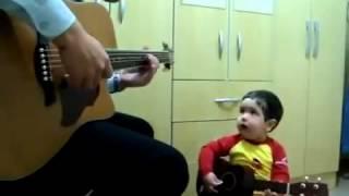 Em bé dễ thương cầm guitar và hát theo bố
