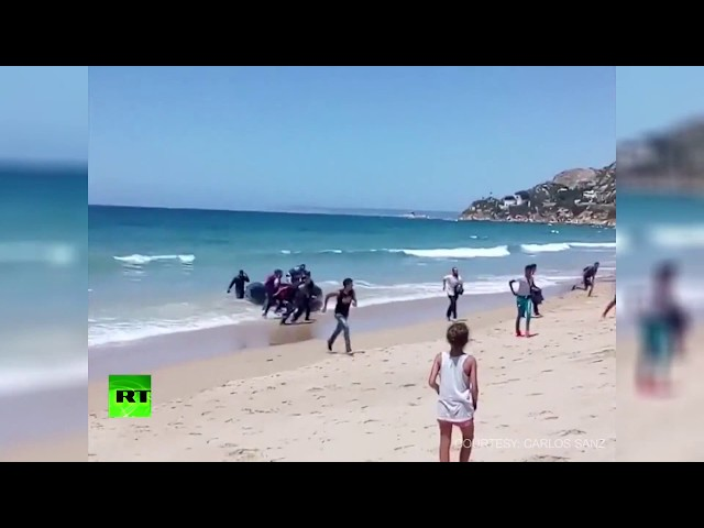 Storm on the beach: Spanish tourists shocked as dinghy full of migrants lands on shore