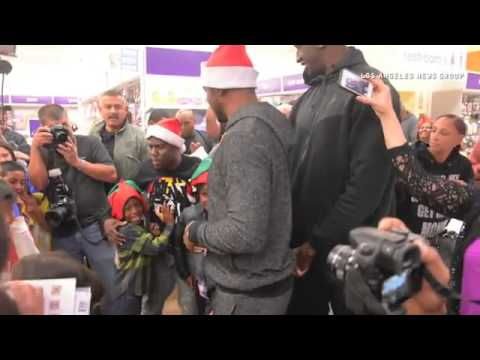 Los Angeles Clipper star Chris Paul, Ekpe Udoh, and actor Kevin Hart, left, hand out gift cards as t