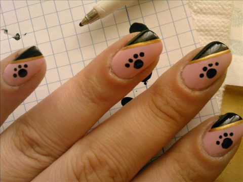 Dog paw print on pink and black nails with golden line.