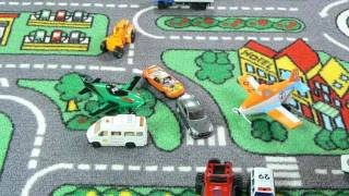 Toy cars riding carpet with roads on it
