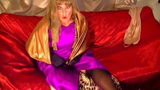 Cross-dresser on couch wearing purple satin bridesmaid dress