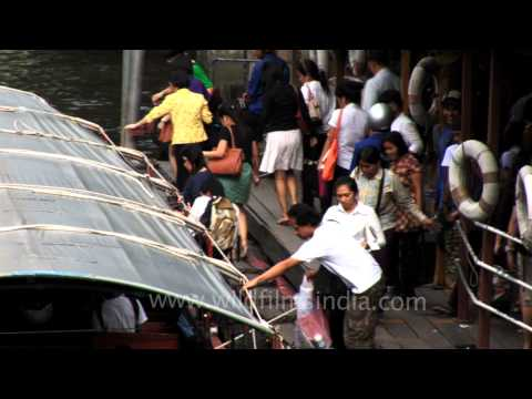 A passing canal boat docked to receive more passengers in Bangkok