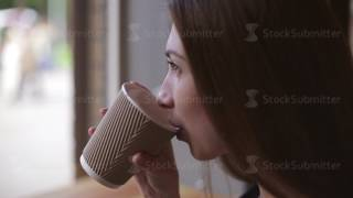 Woman drinking coffee in restaurant or cafe