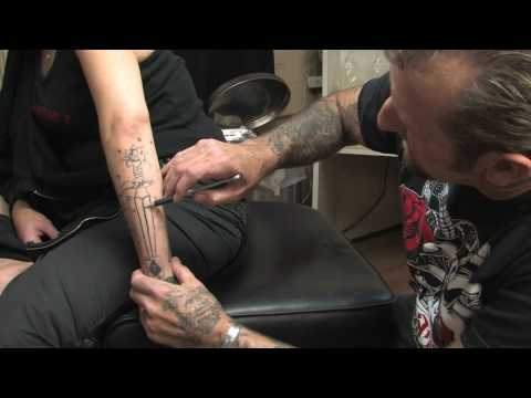 using a homemade ink mixture applied by a handmade rotary tattoo machine