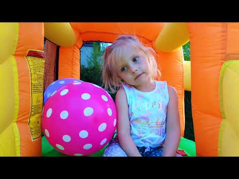 Alisa plays with balloons on the INFLATABLE slide
