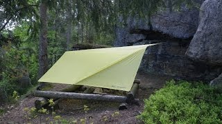 Tarp setup between a stone wall and one tree