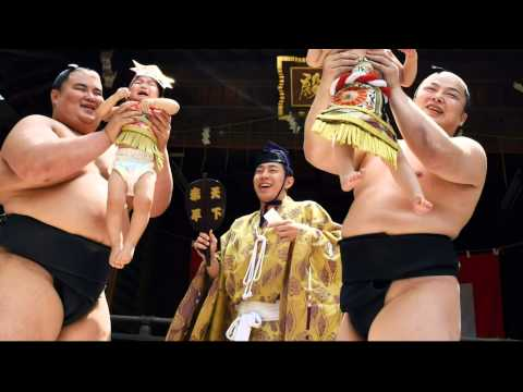 Sumo wrestlers hold screaming babies aloft in ancient crying contest