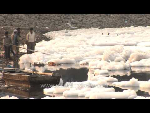 River Yamuna with froth from industrial pollution floating on surface