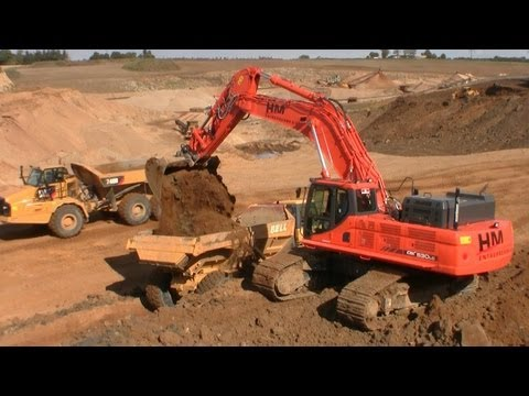 Doosan DX530-3 Excavator Loading Cat And Bell Dumpers