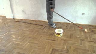 Varnishing parquet floor with roller