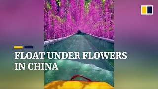 Tourists float under flowers on glass water slide in China