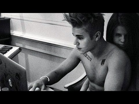 Justin Bieber is shirtless and on his laptop, while Selena embraces him from behind and scowls at the camera...possibly to all his Beliebers. For more Hollyw...